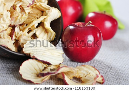 dried apples chips in ceramic bowl with fresh red apples on table