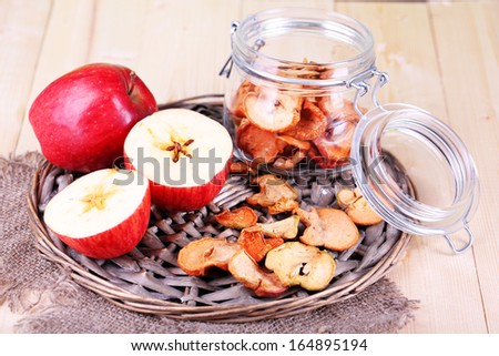 Dried apples in glass jar, on color wooden background - stock photo