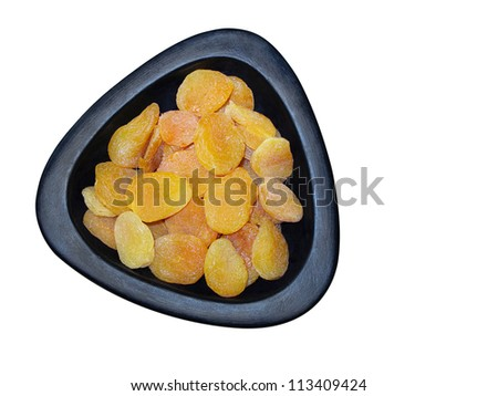 Dried apricots in black triangle shape bowl isolated on white background