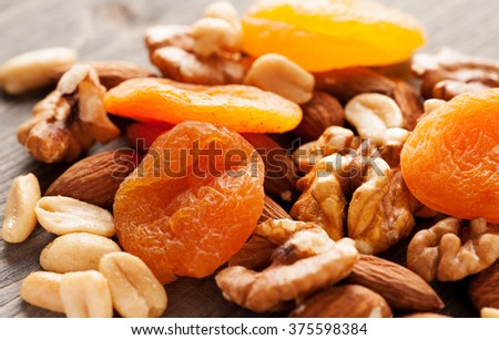 Dried apricots with nuts on wooden table close-up macro shot - stock photo