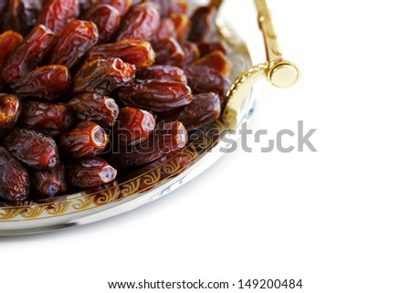 Dried Arabic dates presented on an ornate tray and shot against a white background - stock photo