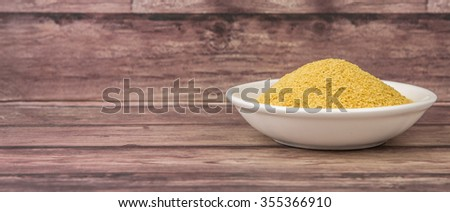 Dried bakers yeast in wooden bowl over wooden background - stock photo