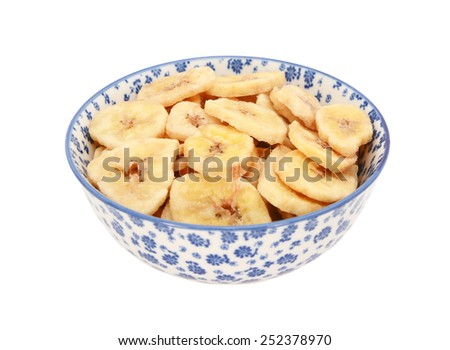 Dried banana chips in a blue and white porcelain bowl with a floral design, isolated on a white background - stock photo