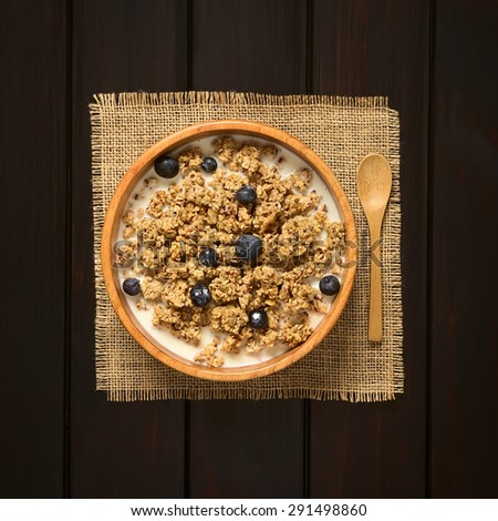 Dried berry and oatmeal breakfast cereal with fresh blueberries and milk in wooden bowl, photographed overhead on dark wood with natural light - stock photo