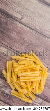 Dried casarecce pasta or long twisted pasta over wooden background