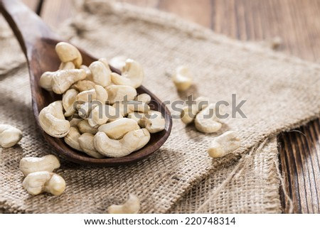 Dried Cashew Nuts on wooden background (close-up shot) - stock photo