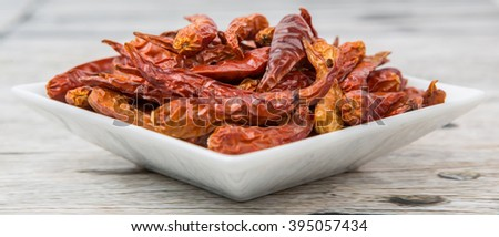 Dried cayenne pepper in a square bowl over wooden background