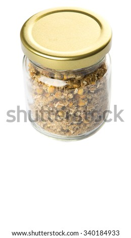 Dried chamomile herbal tea in mason jar over white background
