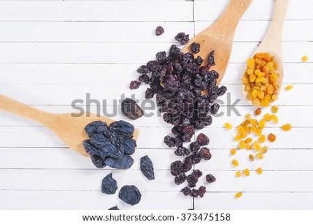 dried cherry, raisin and plum fruits on white wood - stock photo