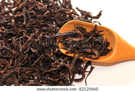 Dried chinese black tea leaves with teaspoon. - stock photo