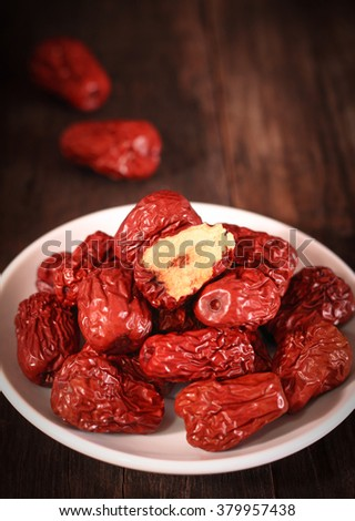 Dried chinese jujubes fruits with white plate on wooden table - stock photo