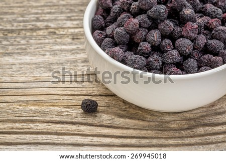 Dried chokeberry (aronia berry) in a small, ceramic bowl against grained wood - stock photo