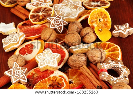 Dried citrus fruits, spices and cookies on wooden table close-up