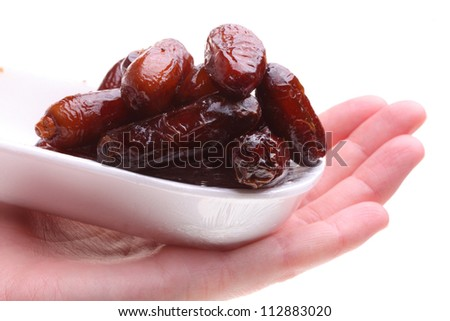 Dried date fruits in hand isolated on white background