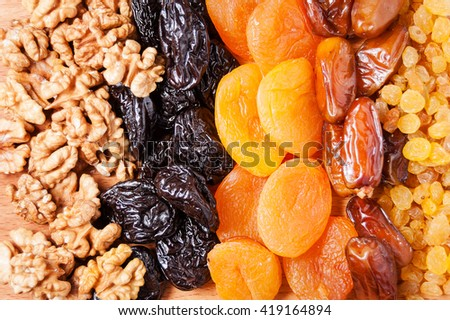 dried dates, figs, raisins, prunes, dried apricots and walnuts on a wooden board - stock photo