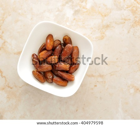 Dried dates fruit in a bowl, on a marble background. top view - stock photo