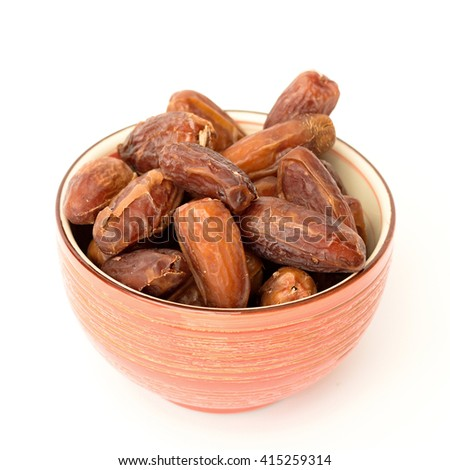 dried dates in a bowl on a white background - stock photo