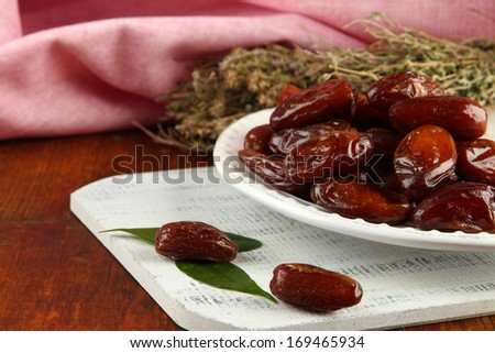 Dried dates on plate on table on fabric background