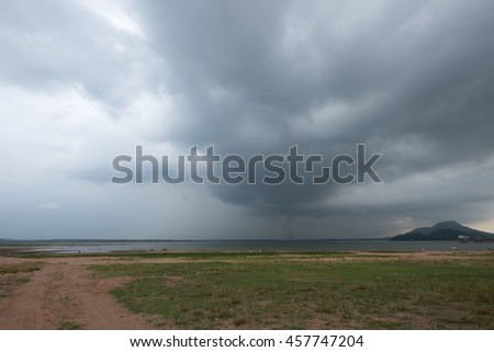 Dried dead tree on grass land with storm rain cloud over the lake. - stock photo