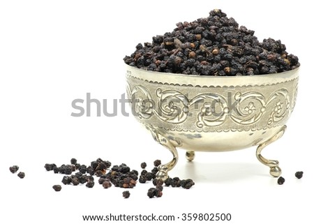 dried elderberries in a silver bowl isolated on white background - stock photo