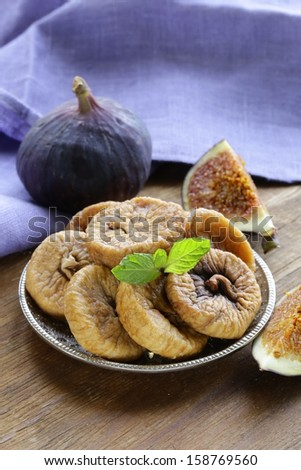 dried figs and fresh fruit on a wooden table - stock photo