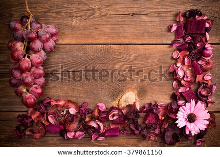 dried flowers and grape fruit on the wooden old table - stock photo