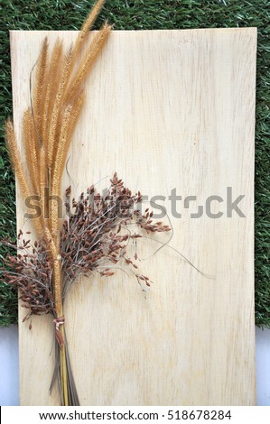 Dried flowers on blank wooden board on green grass background