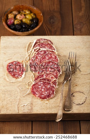 Dried french sausages salami on wooden platter, rustic style - stock photo