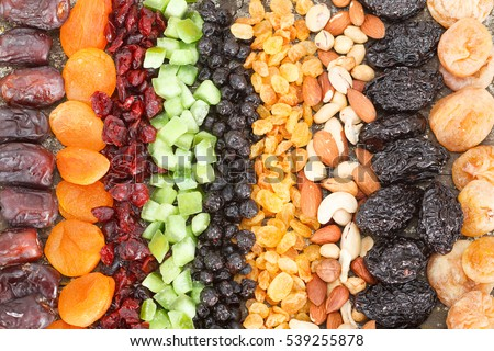Dried fruit background. Rows of dried dates, apricots,cranberries, pomelos, blueberries, nuts, prunes and figs.