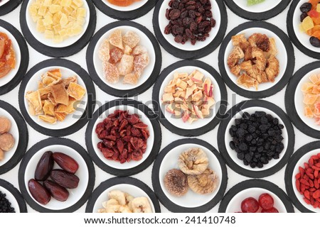 Dried fruit selection in porcelain bowls on slate rounds over white background. - stock photo