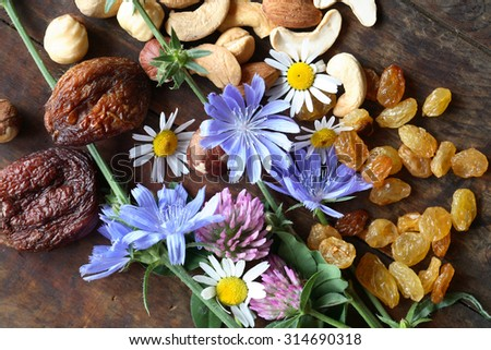 Dried fruits and nuts near wildflowers on wooden board - stock photo