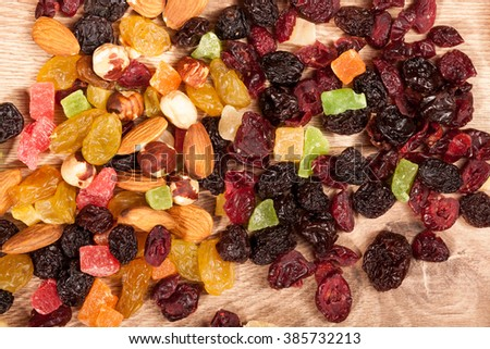 Dried fruits and nuts on wooden background in studio setup. Raw healthy lifestyle