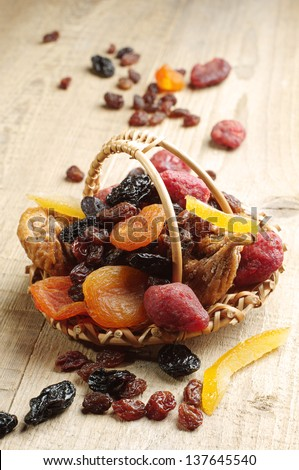 Dried fruits in a basket on a wooden table - stock photo