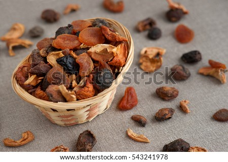 Dried fruits in a wicker basket. Basket with various dried fruits is on sackcloth. Dried fruits scattered on the sackcloth. Dry prunes, apples, apricots, pears need for cooking compote.
