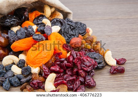 Dried fruits in burlap on wooden background, health food concept.