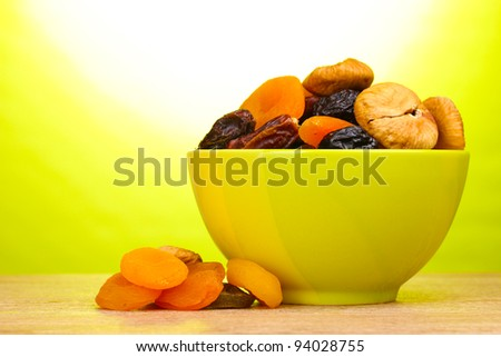 Dried fruits in green bowl on wooden table on green background - stock photo