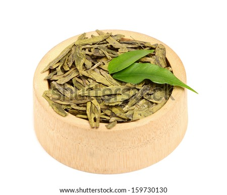 Dried green tea leaves in a wooden bowl isolated on white background.