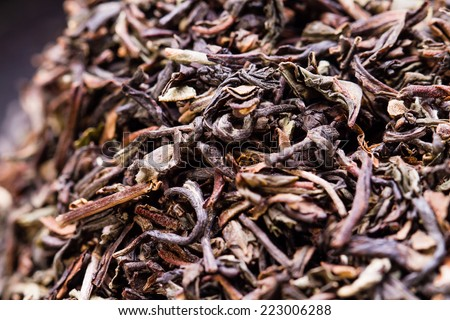 dried green tea leaves on wooden background - stock photo