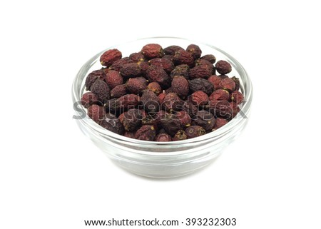 dried hawthorn berries in a glass container on a white background