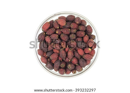 dried hawthorn berries in a glass cup on a white background
