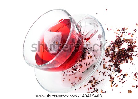 Dried herbal and fruit tea and hot tea with teabag in transparent tea cup isolated on white background. Healthy tea drinking concept.