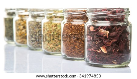 Dried herbal tea lavender, hibiscus, chamomile, linden flower, rooibos, Japanese green tea in mason jars over white background