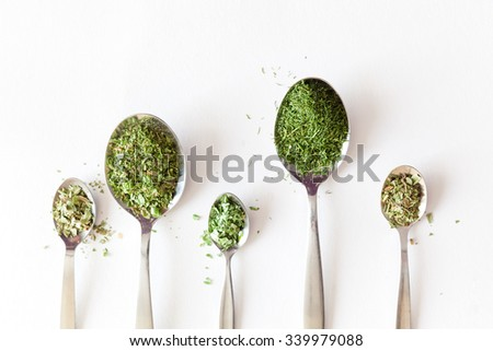 Dried herbs on spoons against natural white background - stock photo