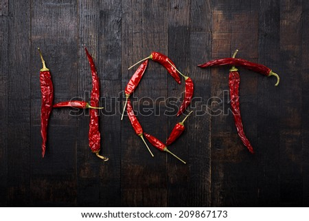 dried hot chili letters on old wooden table