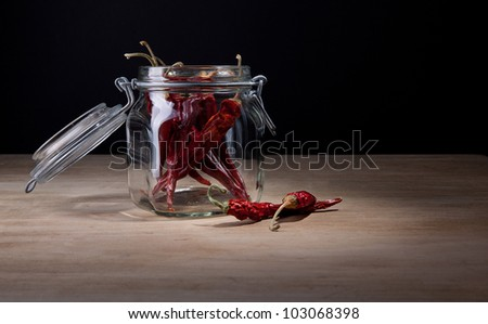 Dried hot red chillies in an opened glass jar with a few lying alongside on the wooden tabletop with copyspace - stock photo