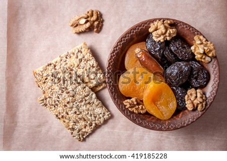 dried in an clay bowl and cookies on the paper, horizontal view - stock photo