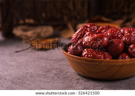 Dried jujube fruit on wooden table - stock photo