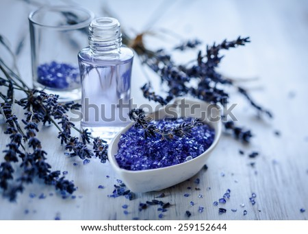 Dried lavender flowers with a bottle of essential oil and salt,toned - stock photo