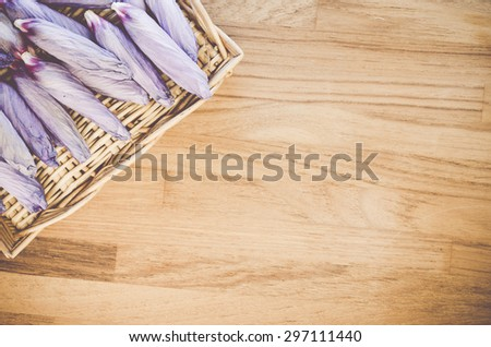 dried light violet hibiscus blossoms and wicker canister on a wood background - stock photo