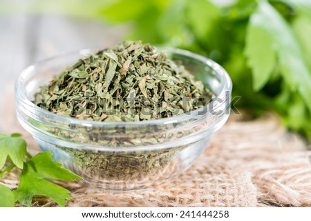 Dried Lovage (detailed close-up shot) with fresh leaves on wood - stock photo